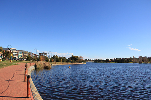 A photo of Yerrabi pond with a path along the side and trees in the background