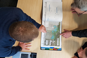 Three people looking at a waterway map