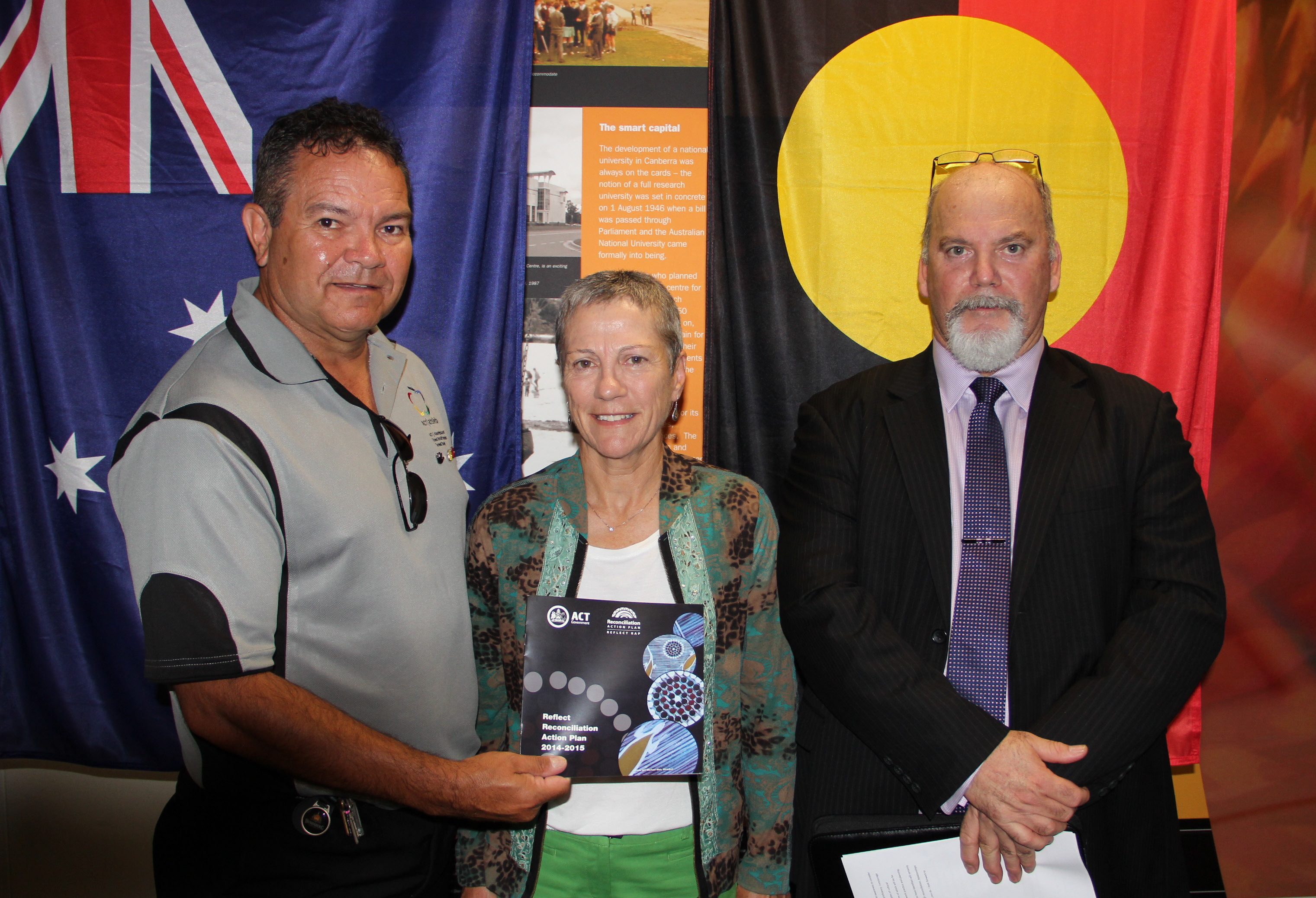 Three people standing infront of the Australian and Aboriginal flag at the launch of the Directorates Action Plan showing a copy of the plan
