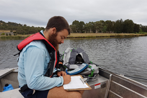 Research officer recording data in a boat on a lake