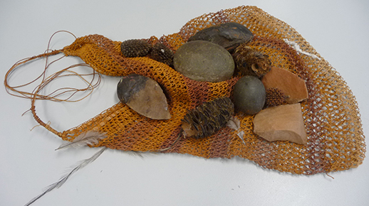 An image of an Aboriginal woven bag and stone tools
